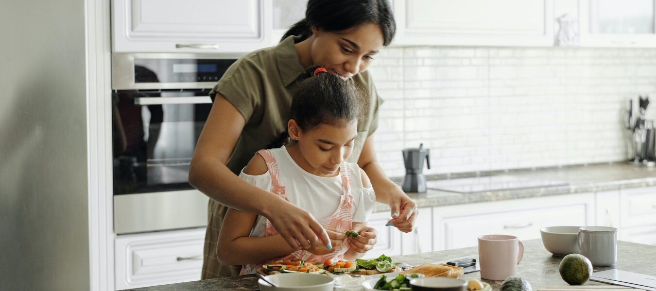 Mother and daughter preparing a meal.