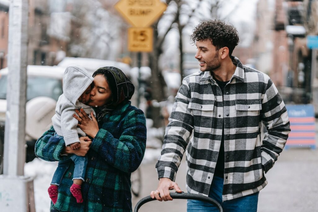 Young family walking outdoors with baby.
