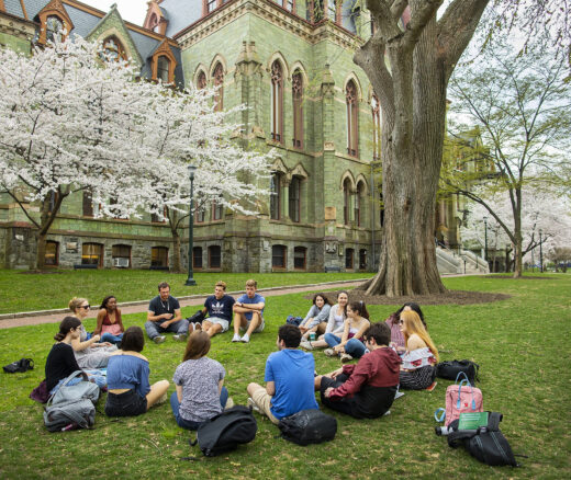 Students sit in circle on Penn campus.