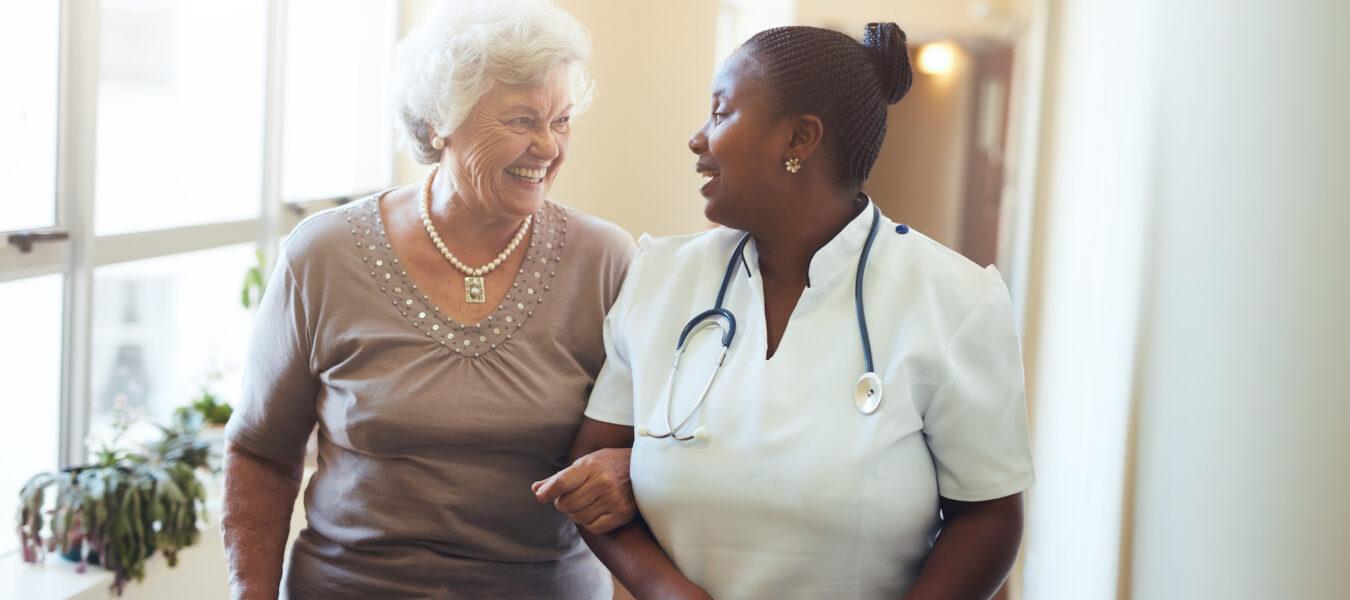 Nurse assisting senior woman at nursing home.