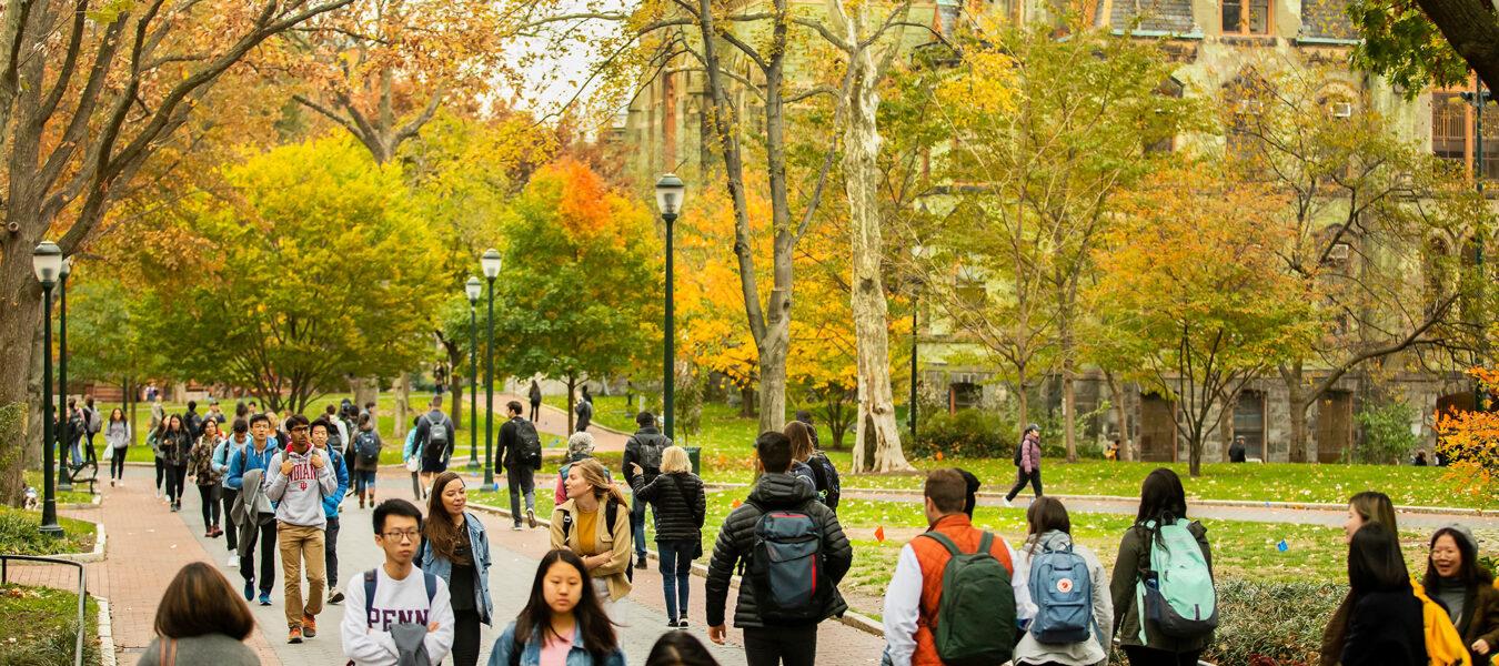 Students walking on Penn Campus Locust Walk in the fall.