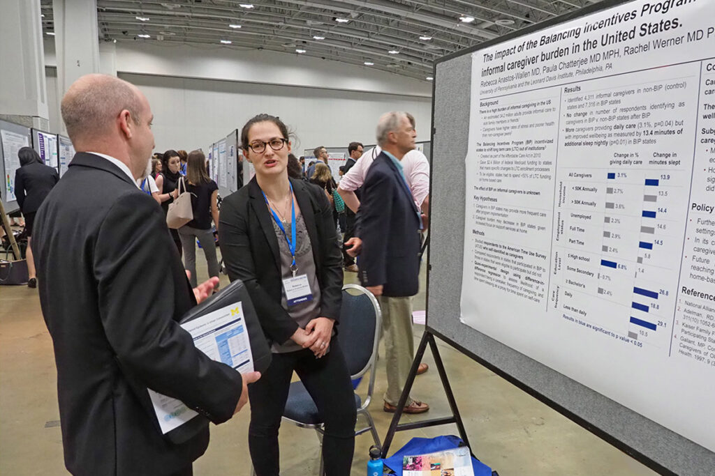 Penn Medicine resident Rebecca Anastos-Wallen, MD, chats about her poster with Andrew Potter, PhD, of the Political Science Department at California State University at Chico.
