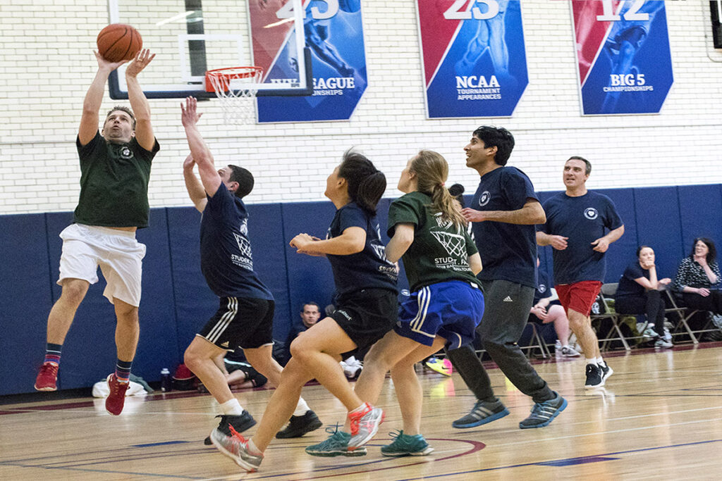 Assistant Penn Professor Matthew Grennan sinks a long one after outjumping PhD student Evan Saltzman in the annual basketball game