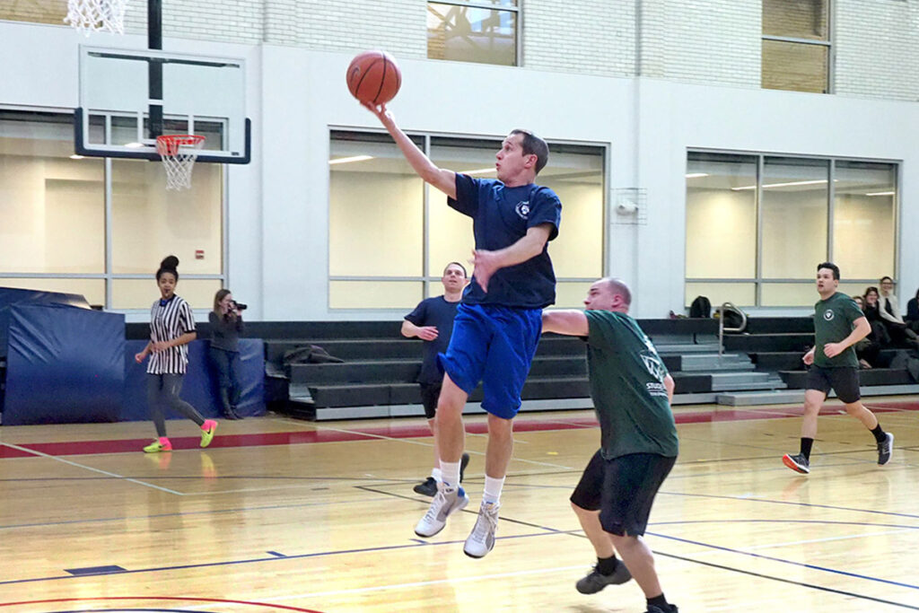 Outracing PhD Student Steve Schwab down the court after a steal, LDI Business Administrator Dan Lynam lifts it at the basket