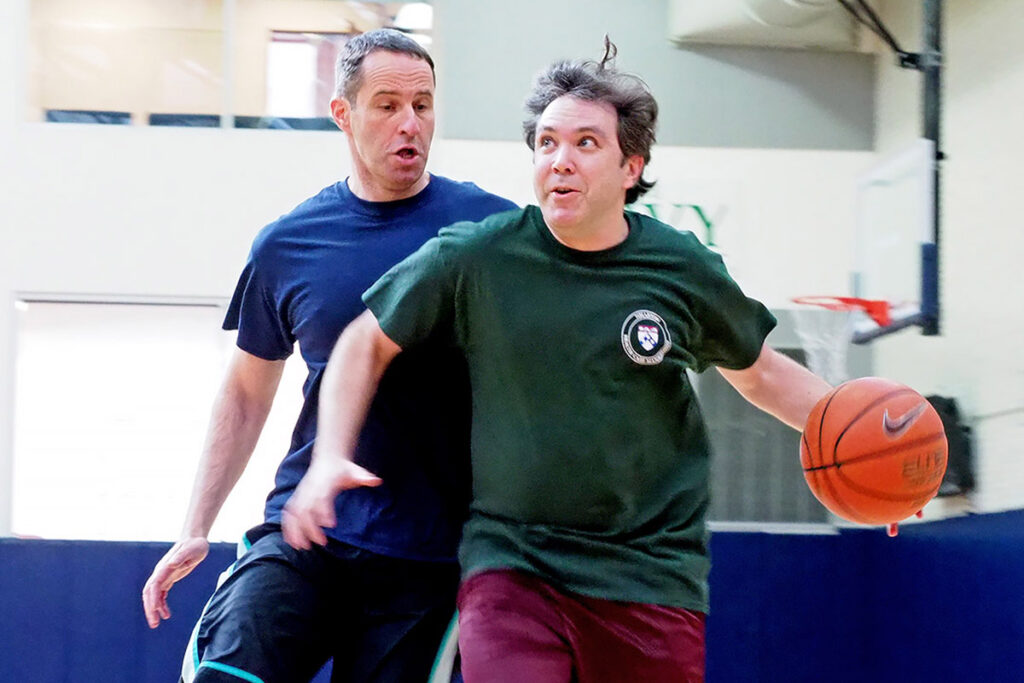 Wharton Associate Professor Guy David and Law School Assistant Professor David Abrams  duel for position and possession on the basketball court