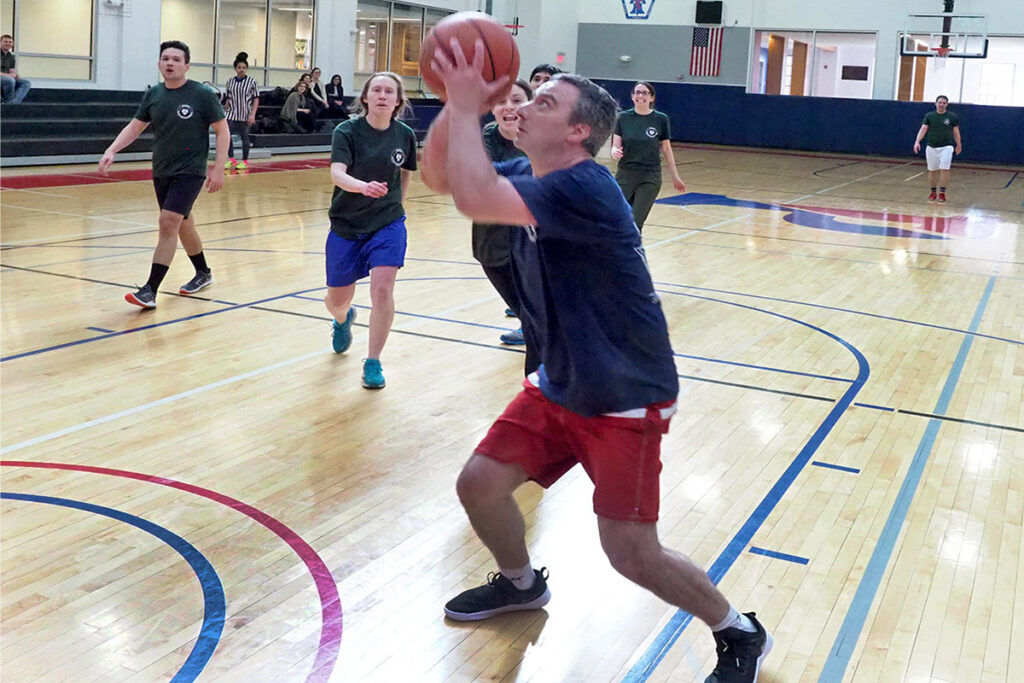 Associate Professor Claudio Lucarelli takes a shot on the basketball court