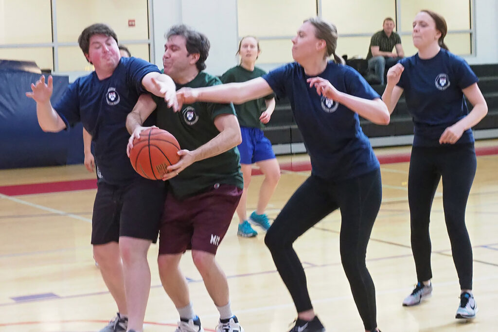 With the score close, Ben Chartock, David Abrams and Sarah Dykstra grapple for possession of the basketball