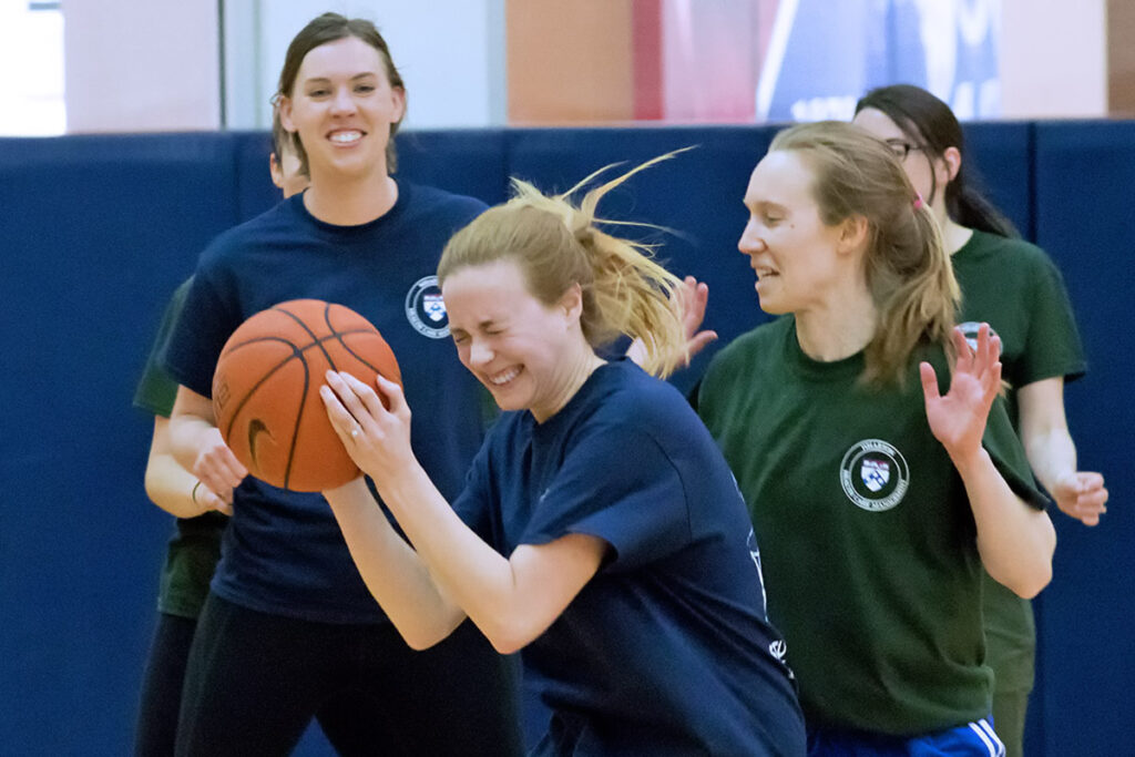 Head down, PhD student Emma Dean bulls her way through the defenders on the basketball court