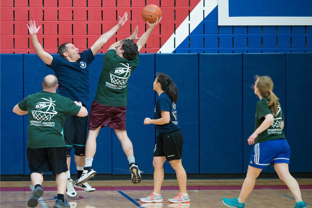 Under the board, Associate Professor Guy David's leaping effort blocks Assistant Law School Professor David Abrams' shot on the basketball court