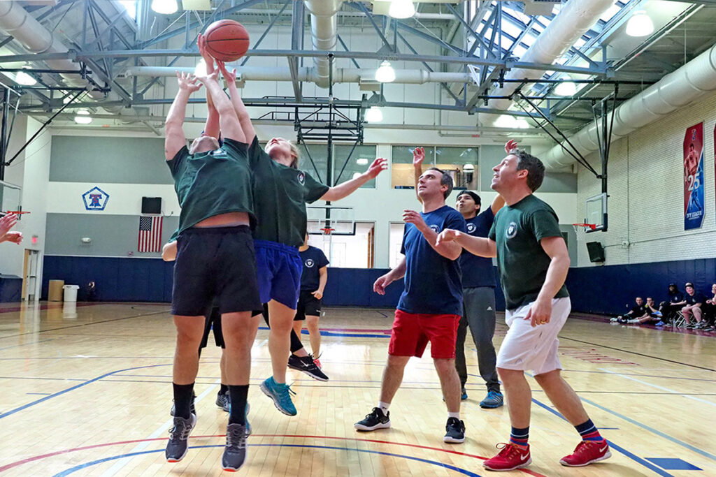 As a basketball foul shot goes awry, PhD students Steve Schwab and Amy Bond lunge upward for the rebound as Claudio Lucarelli, Atul Gupta and Matthew Grennan rush in