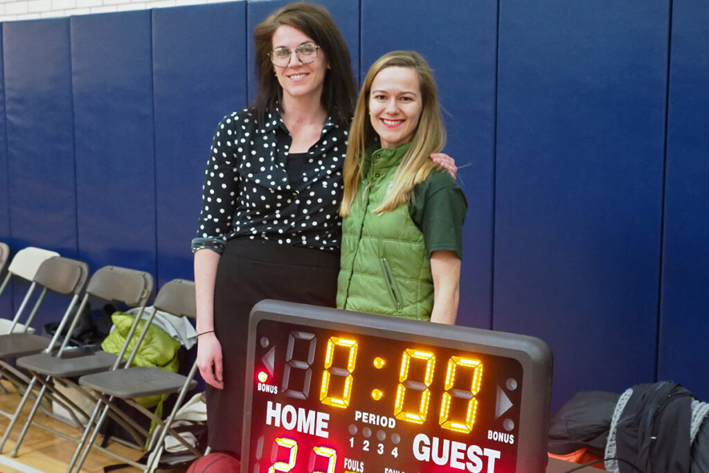 Blue coach Molly Candon and scorekeeper Elena Andreyeva watch as the clock runs out and the Green team wins 29 to 23 in the 2018 annual Wharton student-faculty basketball game