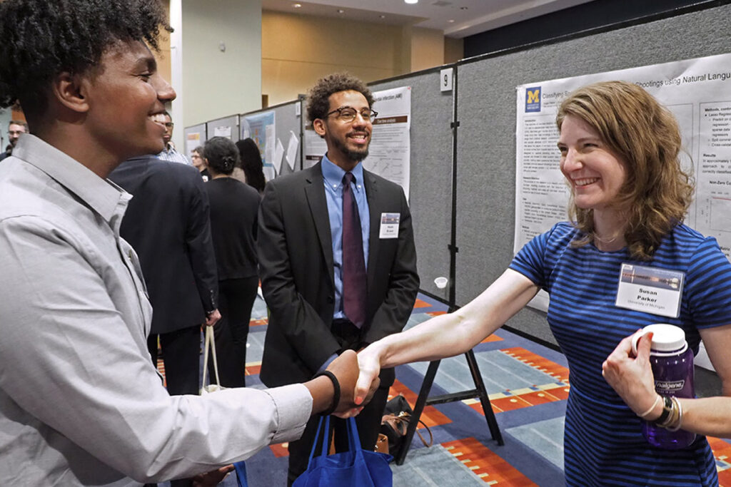 Abeselom Gebreyesus of the University of Maryland and Khalid El-Jack of Boston University greet University of Michigan's Susan Parker, MPP, MS. A PhD candidate in the School of Public Health