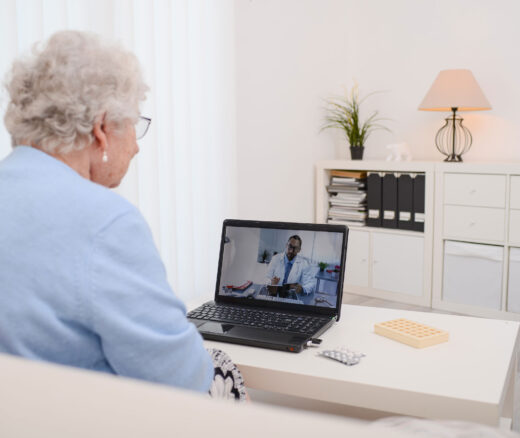 Elderly woman looking at laptop during telemedicine appointment.
