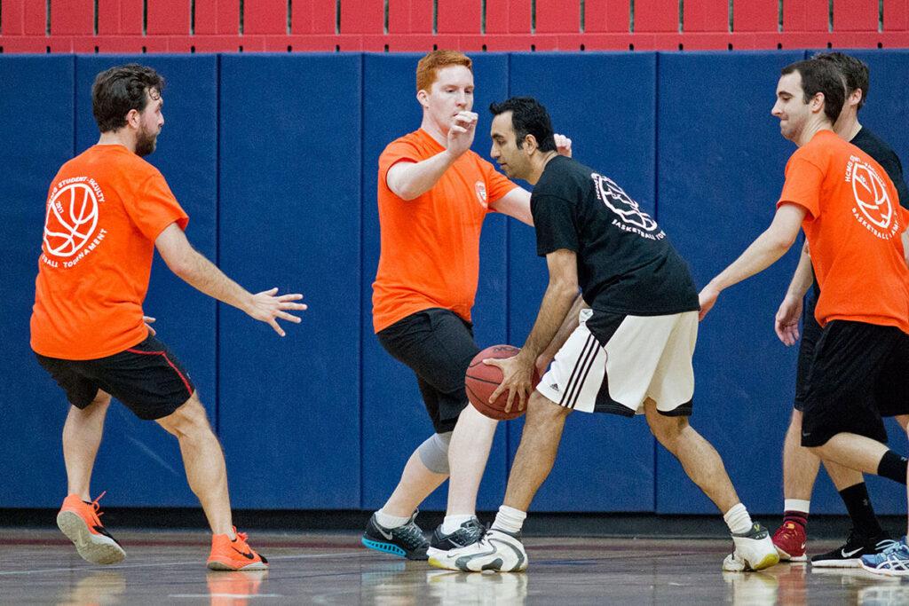 Amol Navathegets cornered by student team playersKyle Myers,Benjamin UkertandJoe Martinez