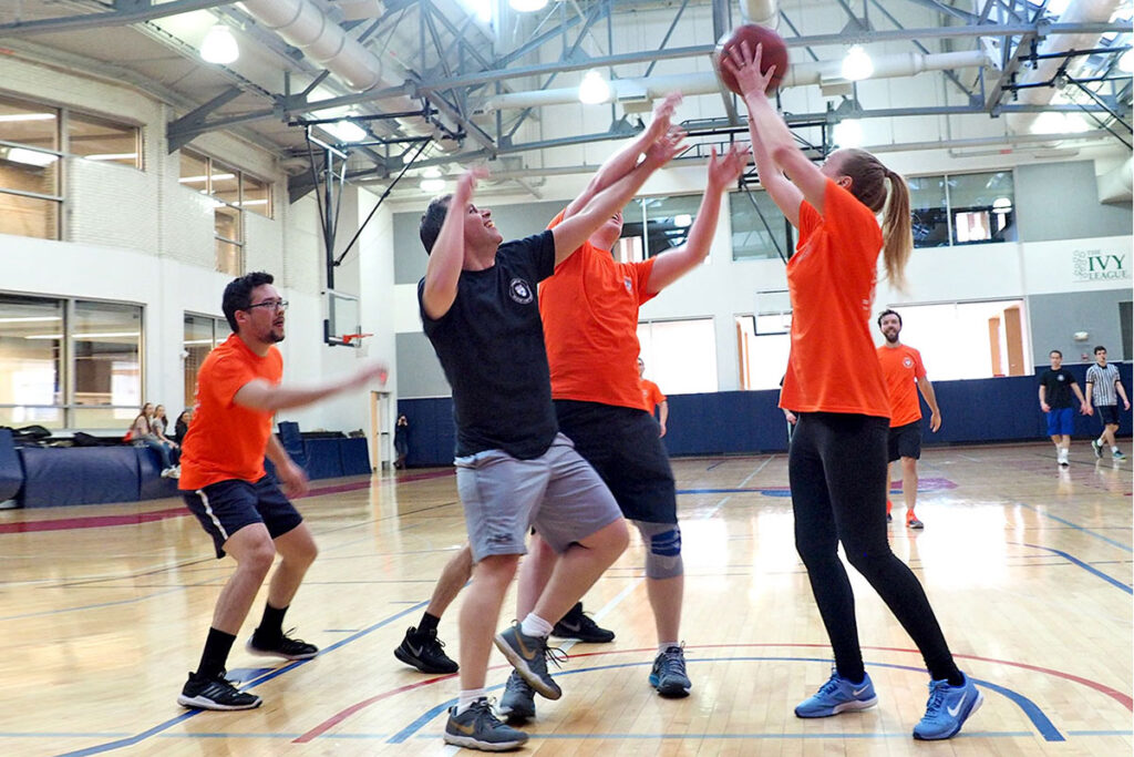 triumphant in her grab for a rebound is studentEmma Deanwho competed for the ball with PhD studentStuart Craig, professorDaniel Polsky, andBenjamin Ukert