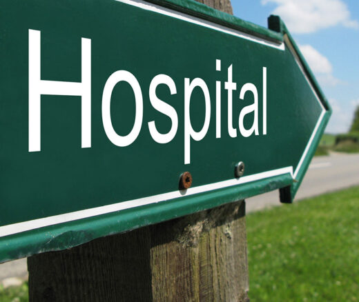 Hospital directional sign on rural street.