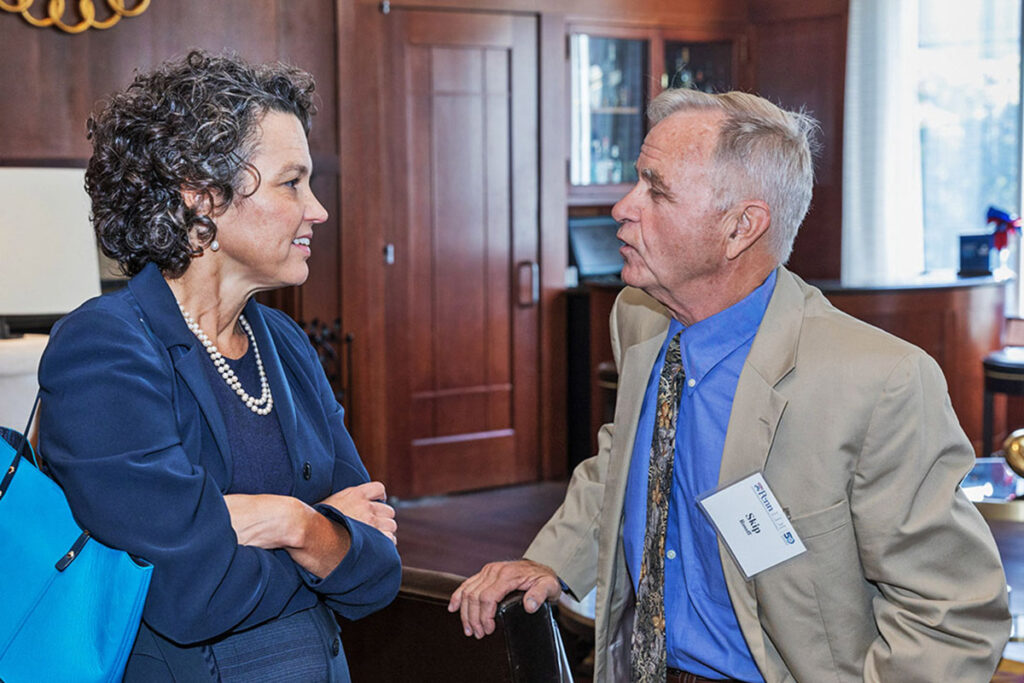 Katrina Armstrong, MD, MSCE, and Arnold (Skip) Rosoff, JD chat at a Penn scientific conference